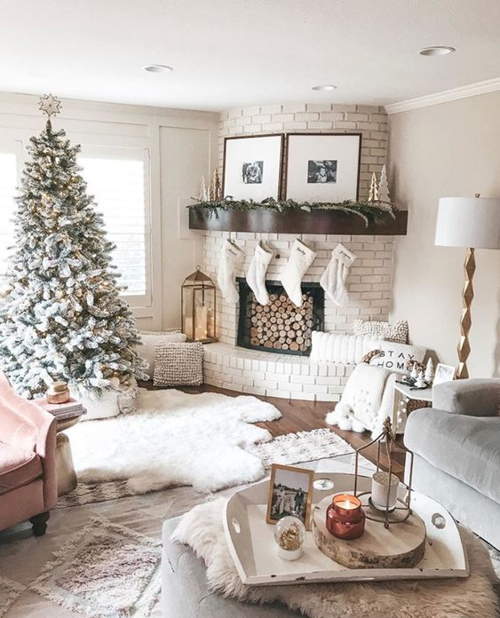 a chic white Christmas living room with a flocked Christmas tree, pompoms, white stockings, faux fur and pillows