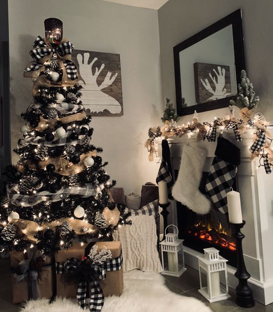 a rustic black Christmas tree with lights, plaid and burlap ribbons, black and white ornaments and snowy pinecones