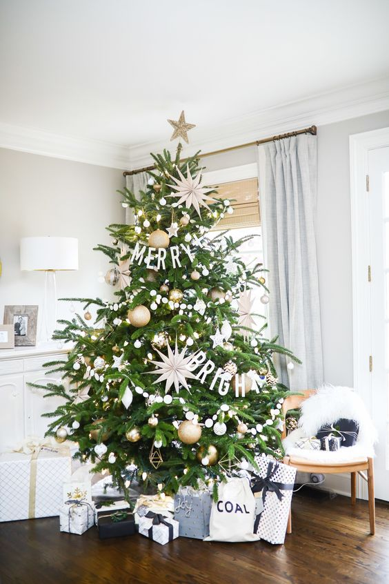 a stylish modern Christmas tree decorated in gold and white, with oversized stars and lights is amazing