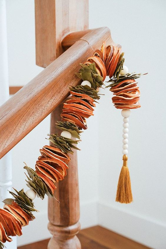 a dried citrus garland with leaves and beads plus a mustard tassel on the end is a cool natural and boho decor idea