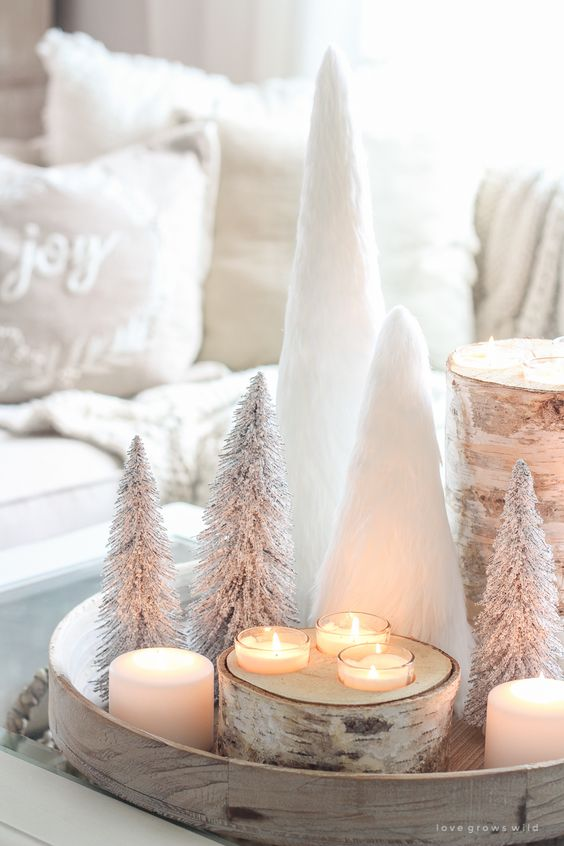 a gorgeous white tray with a tree stump with candles, white candles, mini tabletop Christmas trees is a chic centerpiece or decoration