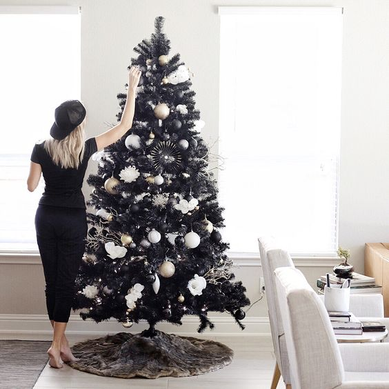 a stylish black and white Christmas tree with black, gold and white ornaments, fluffy toches and paper snowflakes is a chic idea