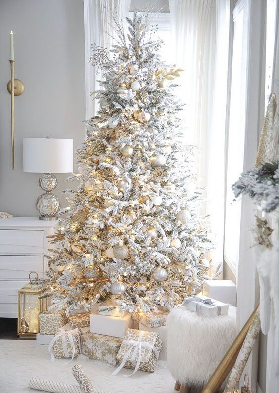 a white Christmas tree decorated with gold and silver ornaments and lights is a very beautiful holiday idea