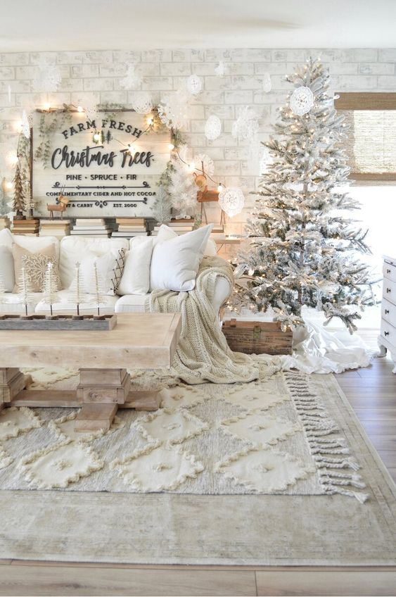 a lovely all neutral Christmas living room with a flocked Christmas tree, white paper snowflakes, white pillows and blankets and some greenery