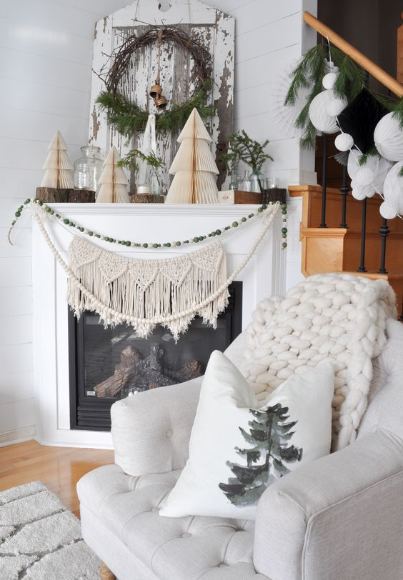 a macrame hanging and a beaded garland on the fireplace, 3D paper trees and branches on the mantel for a natural and boho touch