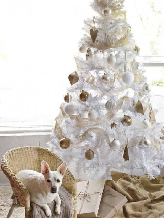 a white Christmas tree decorated with white and gold ornaments, with gold ribbons is ultimate chic and elegance