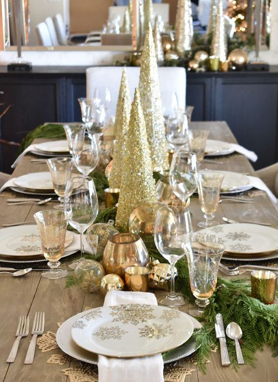 a chic holiday table decorated with gold glitter Christmas trees and metallic candleholders, white porcelain with gold snowflakes is beautiful