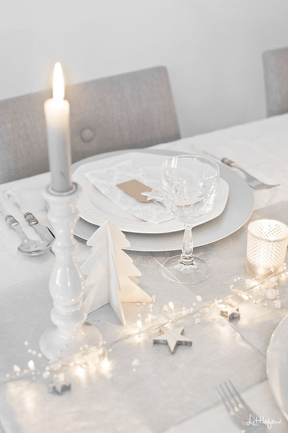 a minimalist white Christmas tablescape with lights, mini stars and beads, candles, white porcelain and white cutlery is chic