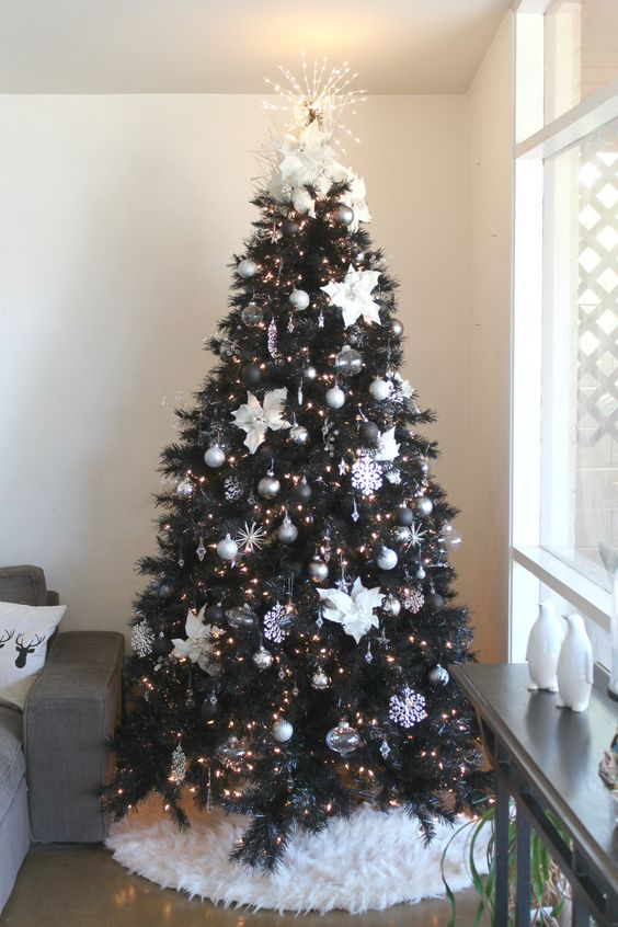 an elegant Christmas tree with silver, black, sheer ornaments, fabric flowers and snowflakes, lights and a lit up topper