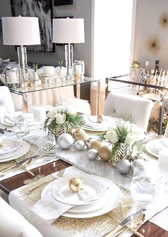 a glam Christmas table setting with white linens, gold placemats and cutlery, white porcelain and white blooms