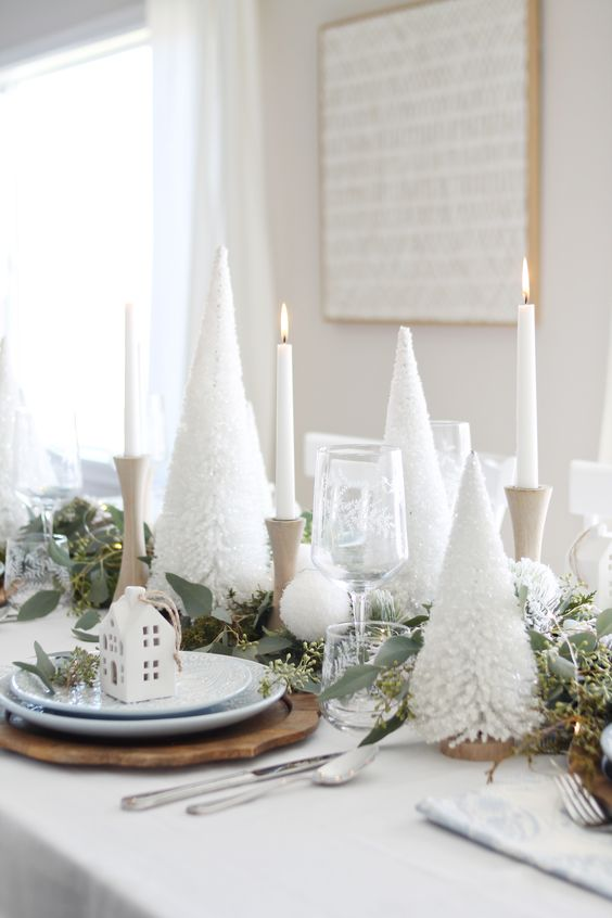 a pretty white Christmas tablescape with bottle cleaner tabletop trees, pompoms, a greenery runner, white house ornaments and wooden chargers