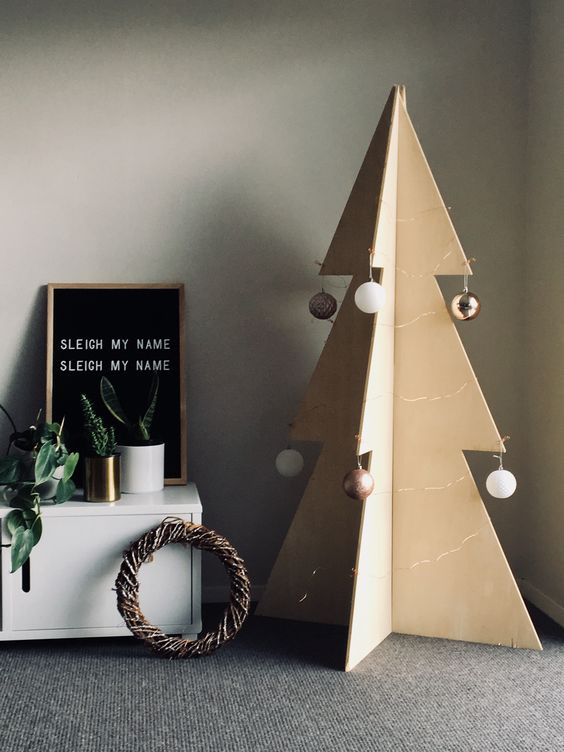 a simple and laconic 3D plywood Christmas tree with metall and white ornaments is a cool idea for a minimlist room
