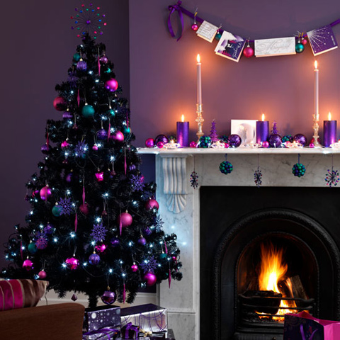a black Christmas tree decorated with pink and purple ornaments, purple snowflakes, green ornaments and lights for splashes of color