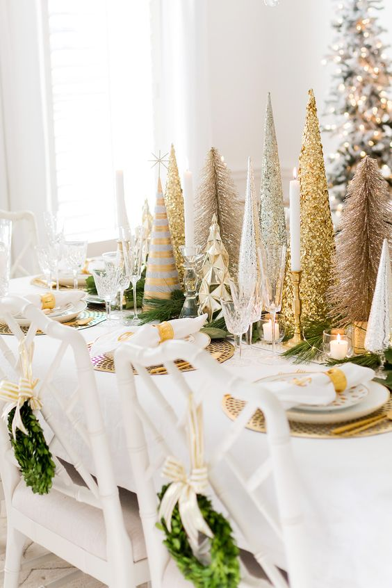 a glam Christmas tablescape done with gold chargers and an arrangement of shiny metallic trees, with gold candleholders and napkin rings and all white everything