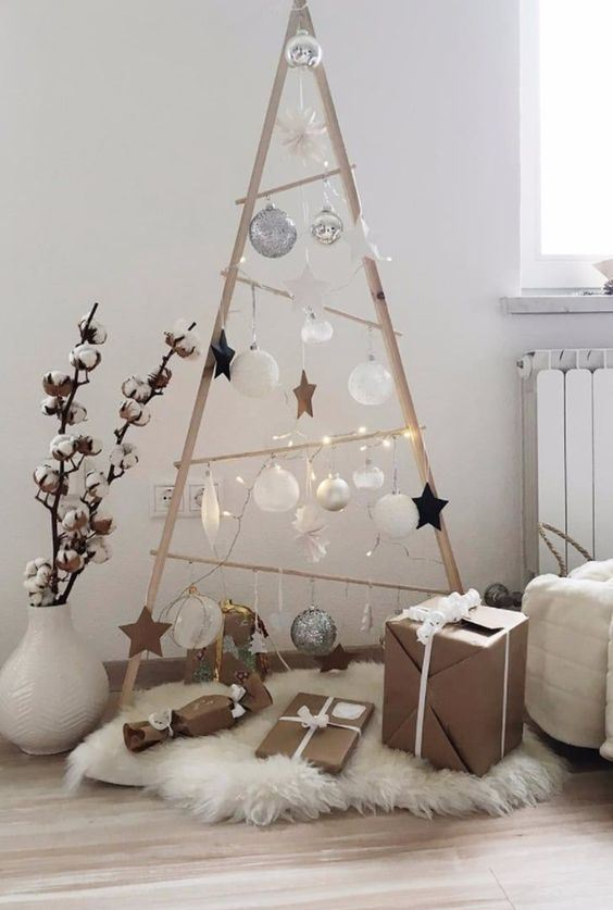 a simple plywood Christmas tree built of planks, with lights, white and silver ornaments and some white faux fur at the base