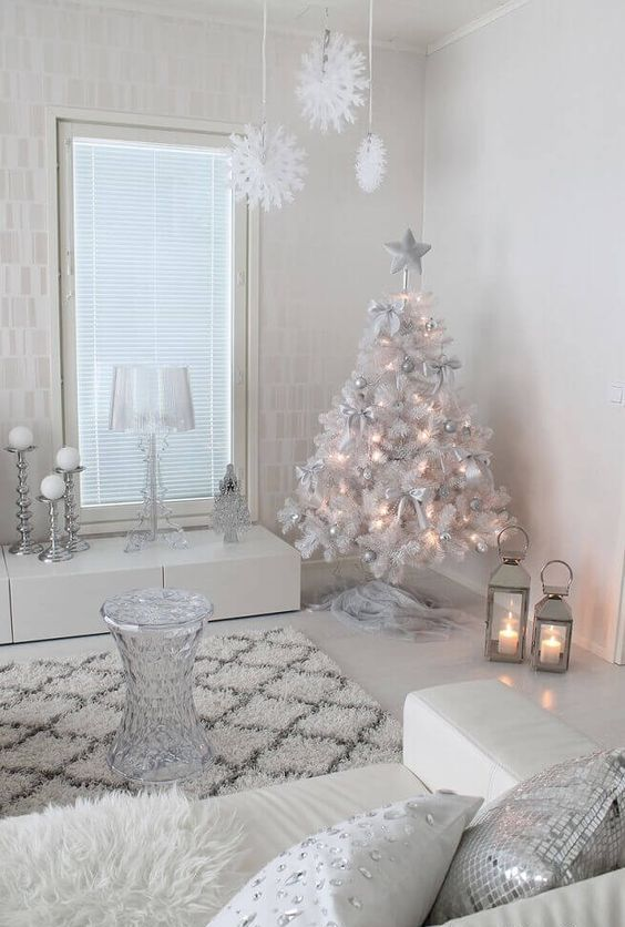 a white and silver living room with a white Christmas tree with lights and silver ornaments, white snowflakes hanging from the ceiling and shiny pillows