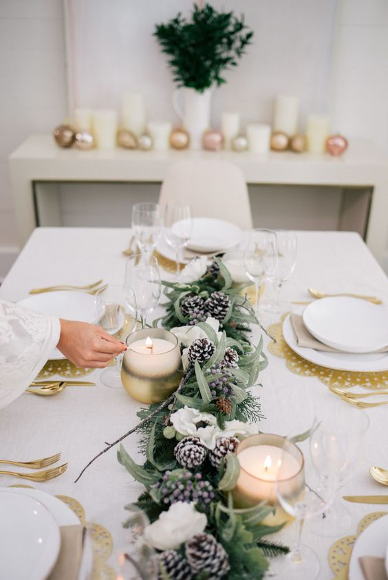 a holiday tablescape with a greenery, snowy pinecone and white bloom garland, candles, gold chargers and cutlery