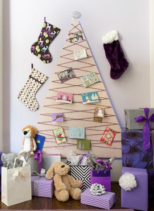 a simple plywood Christmas tree decorated with yarn and vintage Christmas cards plus stockings around is a very eco-friendly idea