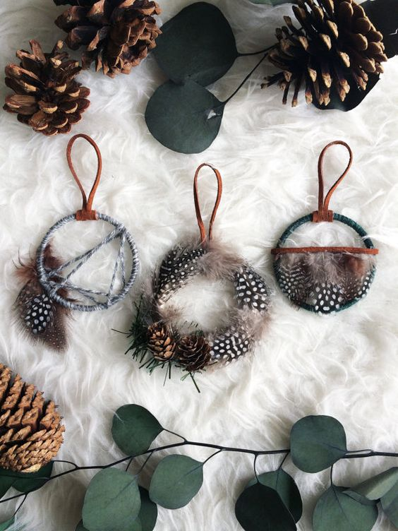 Christmas wreath ornaments made with yarn, feathers, pinecones and greenery are great for boho holiday decor