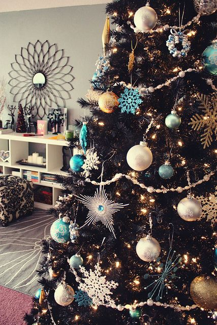 a black Christmas tree with lights, silver and tiffany blue ornaments, snowflakes of various sizes and shiny mini wreaths is chic