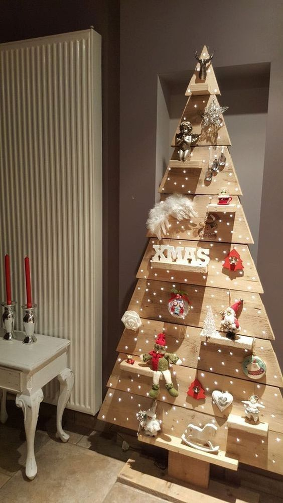 a simple plywood Christmas tree with shelves, feathers, little gnomes, lights and deer heads is amazing