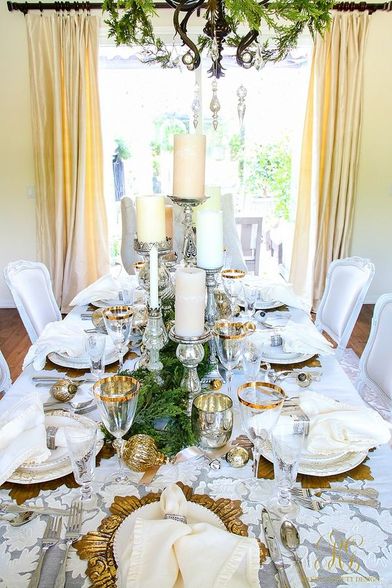 a stylish glam Christmas tablescape with a lace tablecloth, greenery, candles, gold-rimmed glasses and gold chargers