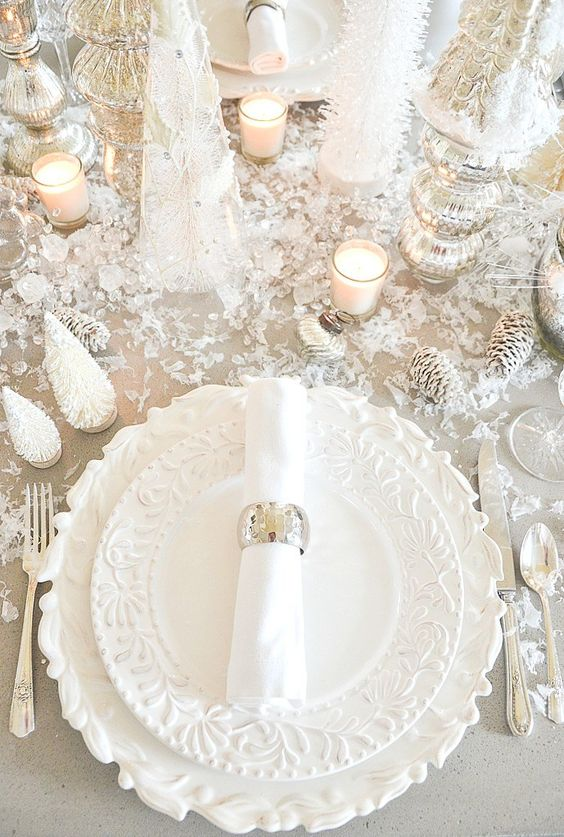 a winter wonderland tablescape with faux snow and ice, elegant plates, silver cutlery, mecurty glass candleholders, snowy pinecones and tabletop trees