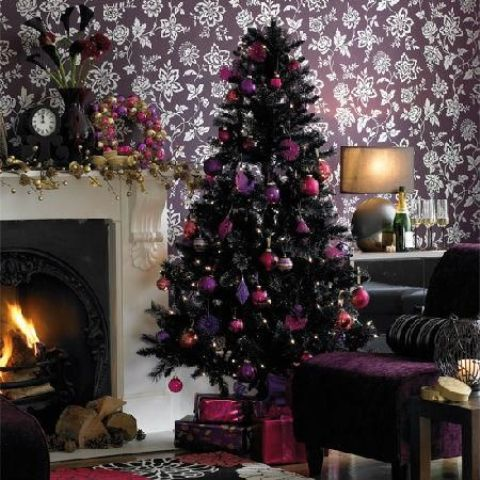 a black Christmas tree with purple, pink and fuchsia ornaments, lights and bows is a bold and chic idea