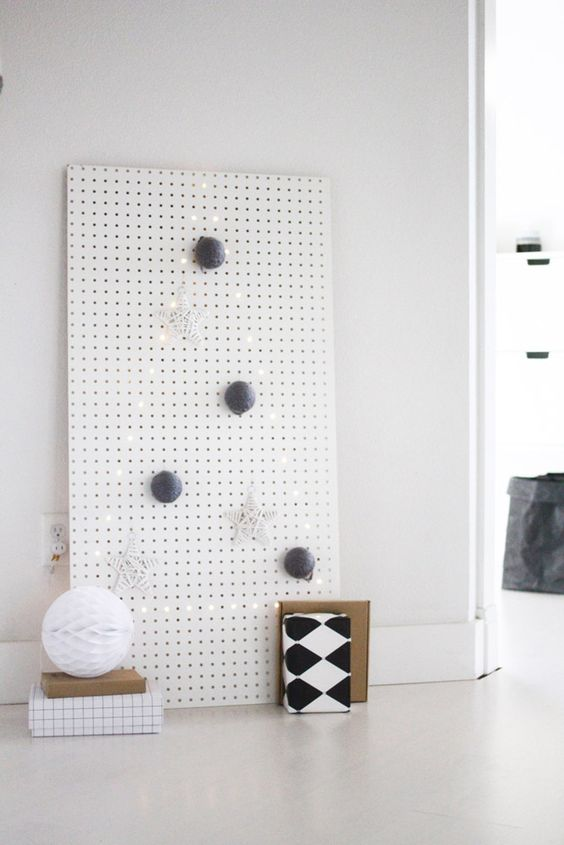 a white pegboard with a Christmas tree lined out with lights and with some ornaments is an ultra-minimalist idea
