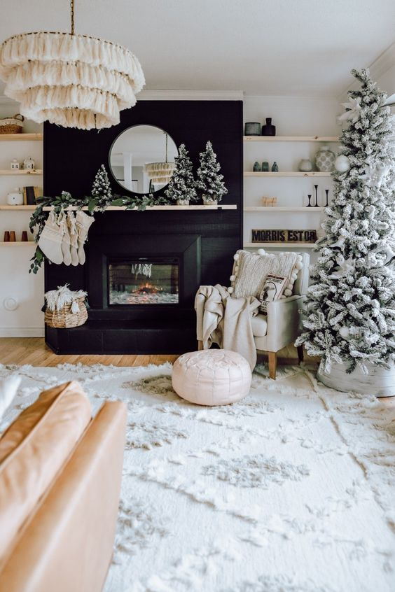 all neutral Christmas decor done with a flocked Christmas tree decorated with white and silver ornaments, white pillows, blankets, stockings and a fir garland