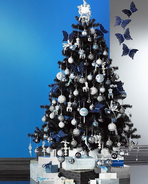 a black Christmas tree with silver and navy ornaments, bows and birds, butterflies and other pretty decor is very elegant