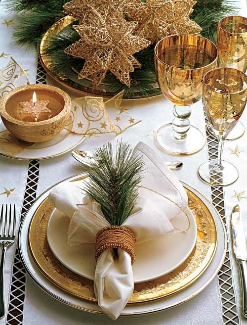 an exquisite gold and white Christmas table with greenery, gold stars, gold glasses and a charger, with fir twigs and a floating candle