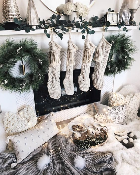 pretty white and neutral Christmas decor with stockings, white blooms, fir wreaths, neutral fluffy pillows, a faux fur rug and pompoms