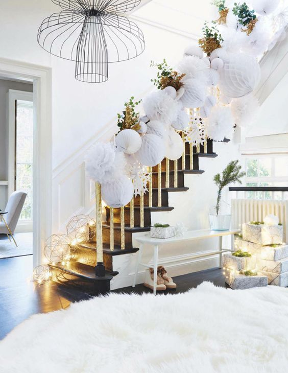 white 3D paper ornaments covering the railing, lights, greenery and a large white faux fur rug and stacks of gifts for a winter wonderland feel