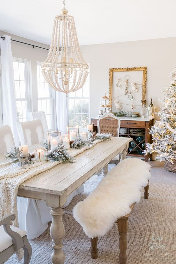 white Christmas decor with faux fur on benches, a white knit runner, candles, flocked fir branches and a white beaded chandelier