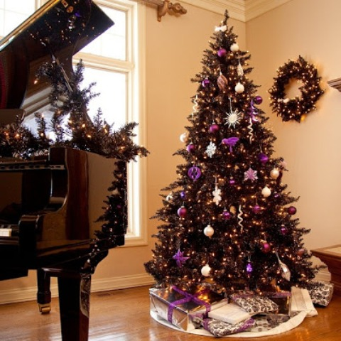 a wreath and tree in black is chic and purple adds just a pop of color to this living room and make it wow