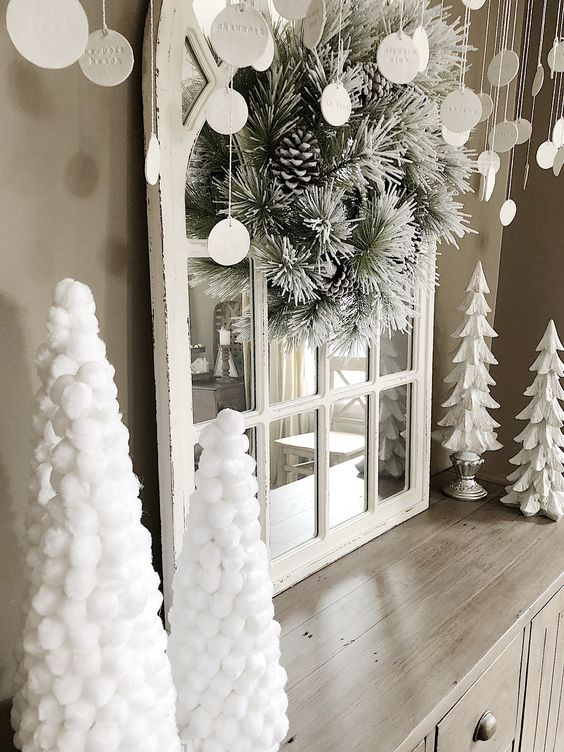white Christmas decor with white paper and pompom Christmas trees, a flocked Christmas wreath with pinecones and clay ornaments with letters