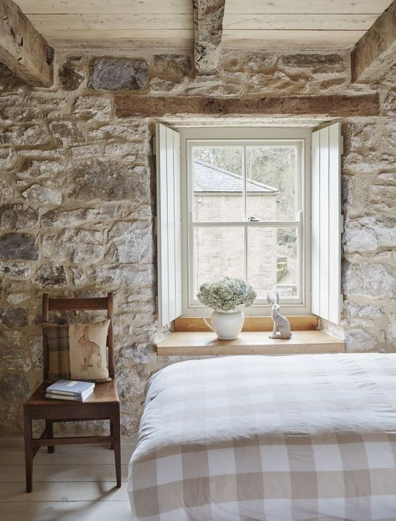 a French farmhouse bedroom with a stone accent wall, vintage furniture and shabby wooden beams that add charm here