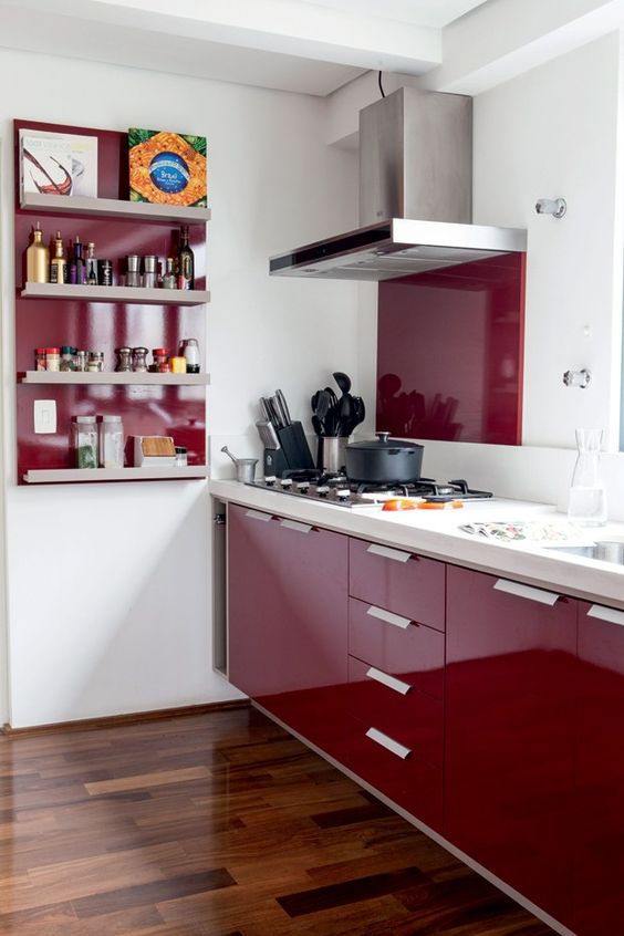 a beautiful deep burgundy contemporary kitchen with a white countertop and a backsplash, a burgundy backsplash and a shelving unit