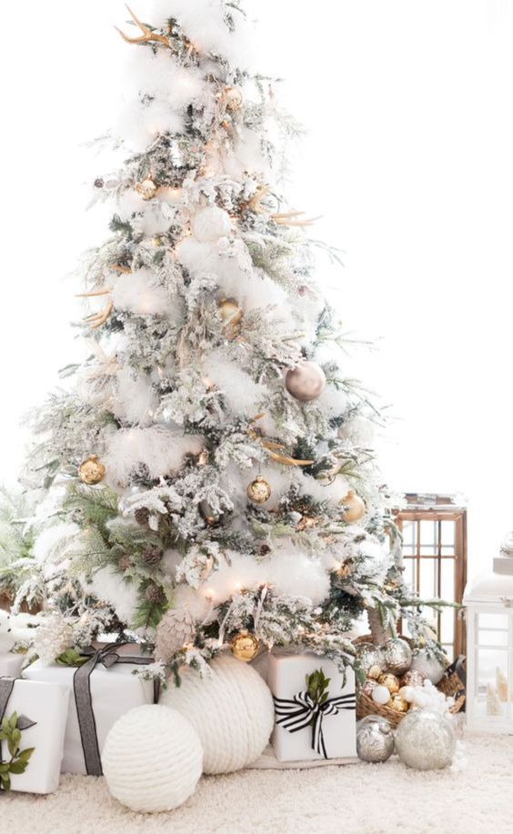 a beautiful modern and a bit woodland flocked Christmas tree with gold and copper ornaments, pinecones and antlers is a very chic idea