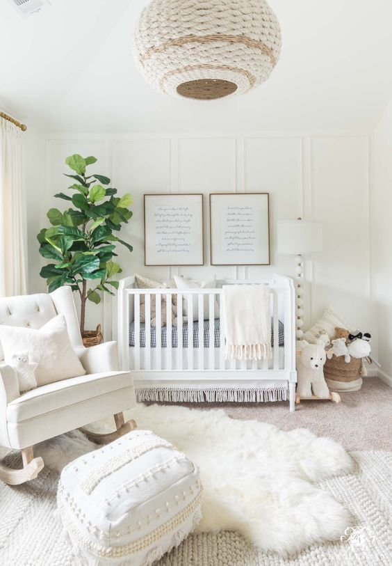 a beautiful neutral nursery with a paneled wall, white furniture, layered rugs, a Moroccan ottoman and a woven pendant lamp