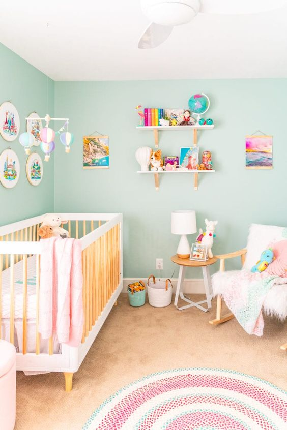 a beautiful nursery with turquoise walls, pink and white bedding, shelves with colorful books and toys and some linens