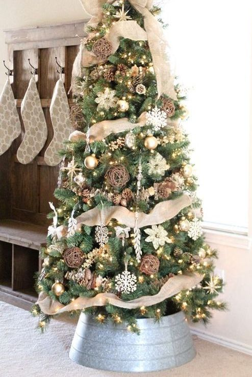 a beautiful rustic Christmas tree with lights, burlap ribbons, vine balls, snowflakes and pinecones and a bucket