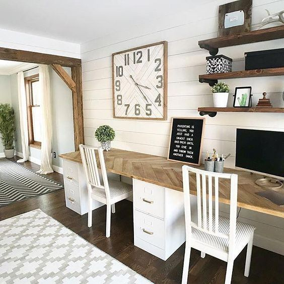 a beautiful rustic home office with a shared desk, open shelves, an oversized clock and a bold artwork is a welcoming space
