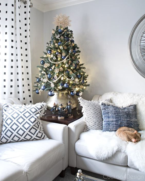 a beautiful vintage-inspired Christmas tree decorated with lights, navy ornaments, beaded garlands, snowflakes and put into a lovely pot