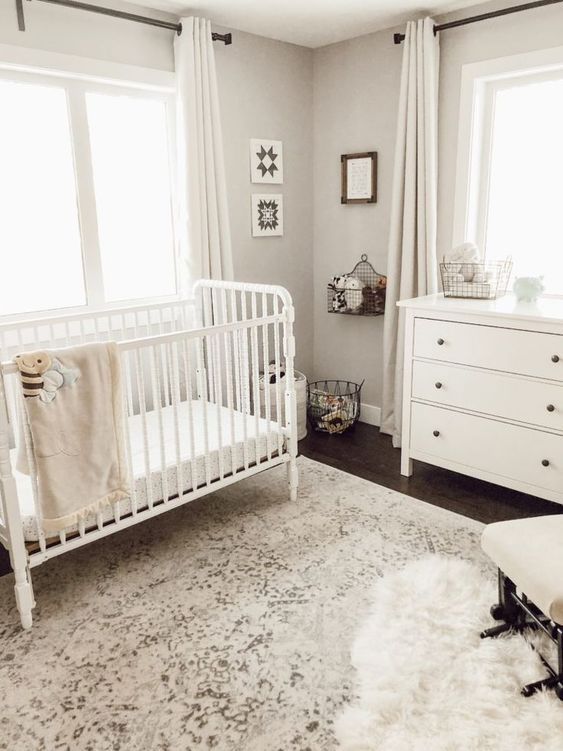 a beautiful vintage nursery in neutrals, with white furniture, white textiles, a chair, layered rugs and some artworks