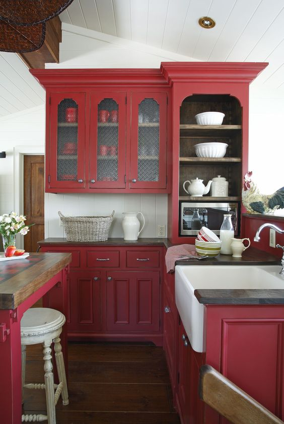 a berry red vintage kitchen with white tiles, black countertops and a vintage table as a table and kitchen island