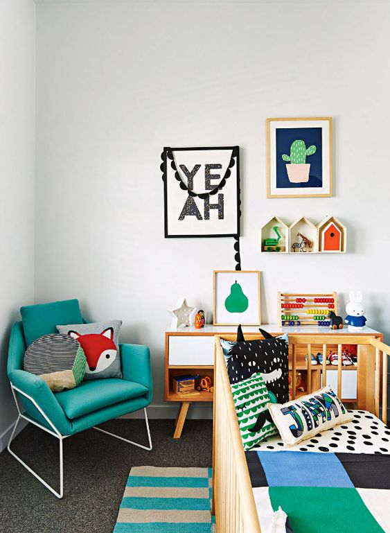 a bold and chic nursery with colorful bedding, toys, artworks, accessories, a turquoise chair and bright house-shaped shelves