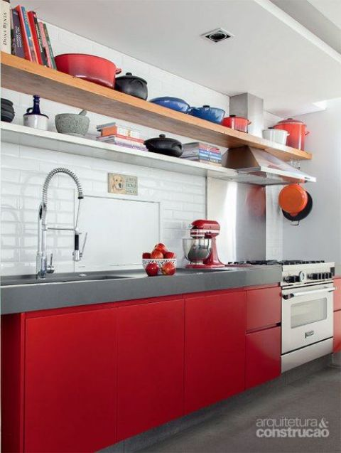 a bold kitchen with sleek red cabinets, a thick concrete countertop, a white tile backsplash and open shelves instead of upper cabinets