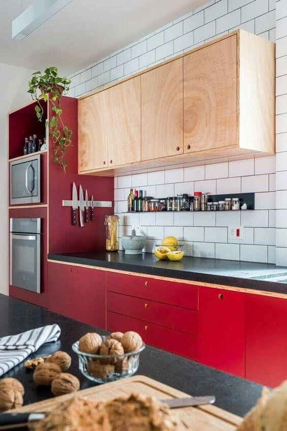 a bold mid-century modern kitchen with bright red lower cabinets and neutral upper ones plus a white tile backsplash